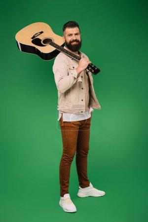 Photo pour Beau guitariste tenant une guitare acoustique, isolée sur vert - image libre de droit