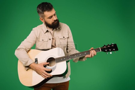 Photo for Handsome bearded man playing on acoustic guitar, isolated on green - Royalty Free Image