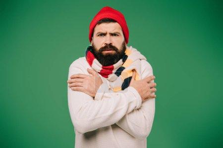 Photo pour Homme barbu en chapeau et écharpe ayant froid isolé sur vert - image libre de droit