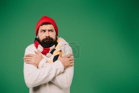 Photo pour Bel homme en chapeau et écharpe ayant froid isolé sur vert - image libre de droit