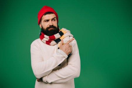 Photo pour Bel homme malade en chapeau et écharpe pointant de côté isolé sur vert - image libre de droit