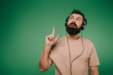 Photo for Bearded man in headphones having idea and pointing up, isolated on green - Royalty Free Image
