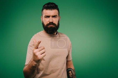 Foto de Guapo hombre barbudo señalando que aislado en verde - Imagen libre de derechos