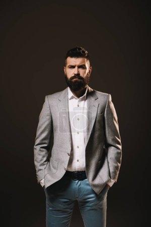 Photo for Beard businessman posing in gray jacket isolated on brown - Royalty Free Image
