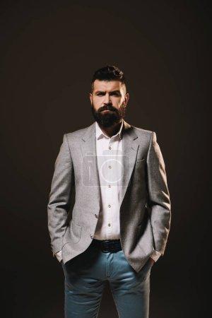 Foto de La barba de hombre de negocios posando en chaqueta gris aislado en marrón - Imagen libre de derechos