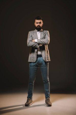 Foto de Apuesto hombre de negocios de pie con los brazos cruzados en marrón - Imagen libre de derechos