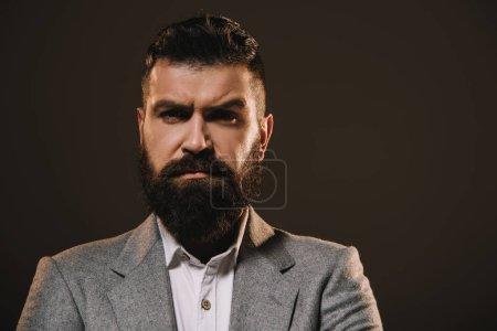 Foto de Apuesto hombre de negocios en chaqueta mirando a cámara aislada en marrón - Imagen libre de derechos
