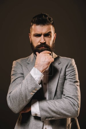 Photo for Handsome beard businessman thinking and looking at camera isolated on brown - Royalty Free Image
