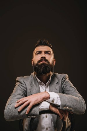 Photo for Handsome thoughtful beard businessman isolated on brown - Royalty Free Image
