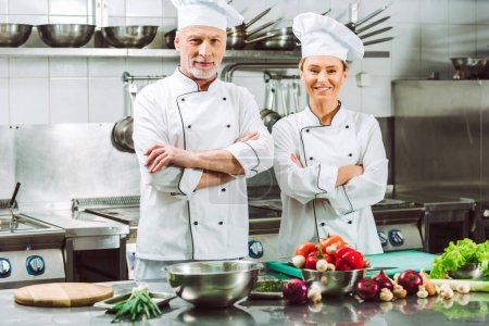 Photo for Female and male chefs in uniform with arms crossed during cooking in restaurant kitchen - Royalty Free Image