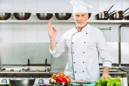 Photo for Handsome smiling male chef in uniform looking at camera and showing ok sign in restaurant kitchen - Royalty Free Image