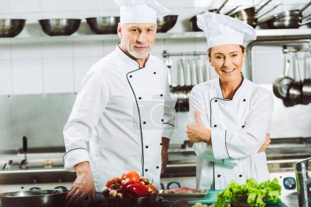 Photo for Smiling female and male chefs in uniform and hats looking at camera while cooking in restaurant kitchen - Royalty Free Image