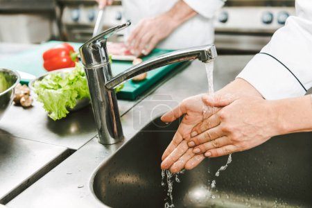 Photo for Cropped view of female chef washing hands over sink in restaurant kitchen - Royalty Free Image