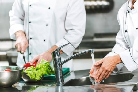 cropped view of female chef washing hands over sink while colleague cooking on background in restaurant kitchen