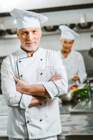 Photo for Handsome male chef in uniform with arms crossed looking at camera in restaurant kitchen - Royalty Free Image