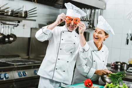Photo for Smiling female cook looking at male chef holding pepper slices in front of face in restaurant kitchen - Royalty Free Image
