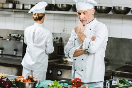 Photo for Pensive male chef in double-breasted jacket during cooking in restaurant kitchen with female colleague on background - Royalty Free Image