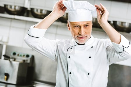 Photo for Handsome male chef in uniform adjusting cap in restaurant kitchen - Royalty Free Image