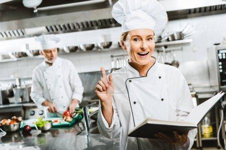 Foto de Hermosa mujer chef en uniforme sosteniendo el libro de recetas y haciendo gesto de idea en cocina de restaurante con colega en el fondo - Imagen libre de derechos