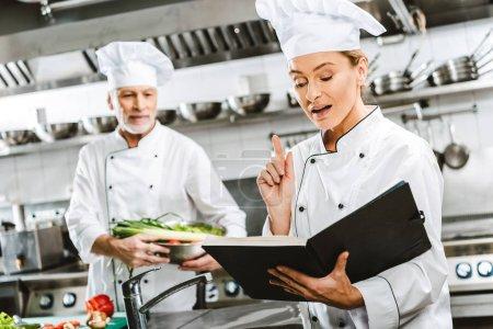 Foto de Mujer chef en uniforme sosteniendo el libro de recetas y haciendo gesto de idea mientras colega cocina experiencia en cocina de restaurante - Imagen libre de derechos
