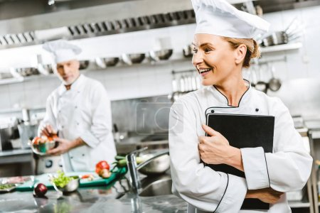 beautiful female chef in uniform holding recipe book in restaurant kitchen with colleague on background
