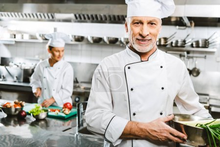 Photo for Handsome male chef in uniform looking at camera while colleague cooking on background in restaurant kitchen - Royalty Free Image