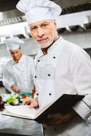 Photo for Male chef in uniform and hat looking at camera and holding recipe book in restaurant kitchen - Royalty Free Image