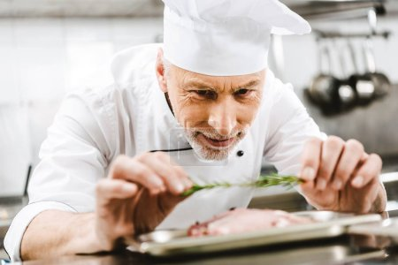 Photo for Male chef in uniform decorating dish with herb in restaurant kitchen - Royalty Free Image
