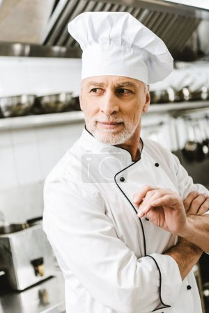 Photo for Handsome male chef in uniform and cap looking away in restaurant kitchen - Royalty Free Image