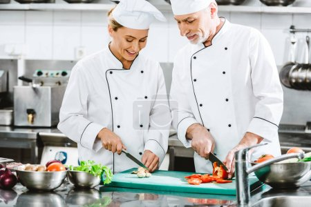 Photo for Male and female chefs in double-breasted jackets preparing food in restaurant kitchen - Royalty Free Image