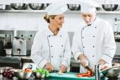 """Постер, картина, фотообои """"женский и мужской поваров в единообразных резка ингредиенты во время приготовления пищи в кухне ресторана"""""""