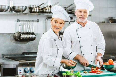 Photo for Female and male chefs in uniform looking at camera while cutting ingredients duting cooking in restaurant kitchen - Royalty Free Image