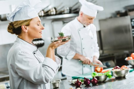 Photo for Female chef in uniform holding meat dish on plate with male colleague cooking on background in restaurant kitchen - Royalty Free Image