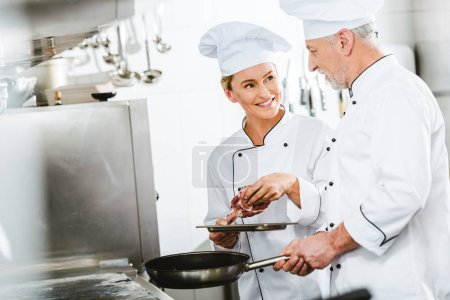 Photo for Female and male chefs in uniform cooking meat on pan in restaurant kitchen with copy space - Royalty Free Image