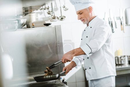 Photo for Male chef roasting meat steak in restaurant kitchen - Royalty Free Image