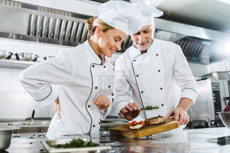 Photo for Female and male chefs in uniform with meat steak on wooden board in restaurant kitchen - Royalty Free Image