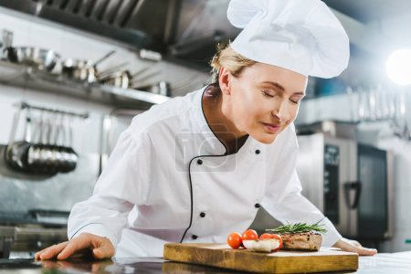 Photo for Beautiful female chef in uniform enjoying aroma of meat steak on wooden board in restaurant kitchen - Royalty Free Image