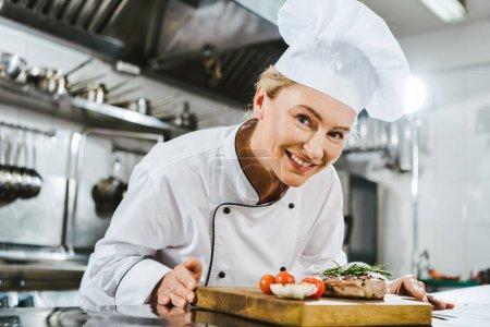 Photo pour Belle chef féminine en uniforme tenant steak de viande avec romarin sur planche en bois dans la cuisine du restaurant - image libre de droit