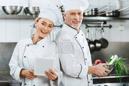 female and male chefs in iniforms looking at camera and using digital tablet while cooking in restaurant kitchen