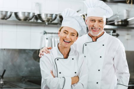 Photo for Female and male chefs in uniform looking at camera and laughing at restaurant kitchen - Royalty Free Image