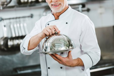 Photo for Cropped view of male chef in uniform holding serving tray with dome in restaurant kitchen - Royalty Free Image