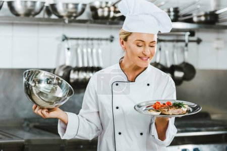 Photo for Selective focus of beautiful female chef in uniform holding serving tray with meat dish in restaurant kitchen - Royalty Free Image