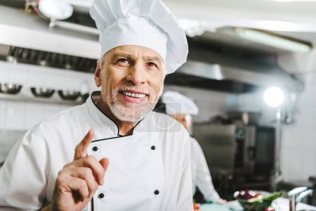 Photo for Handsome smiling male chef in uniform and cap doing idea gesture in restaurant kitchen - Royalty Free Image