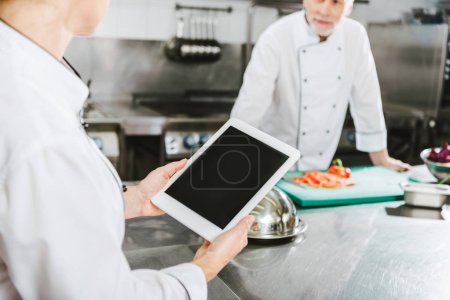 Photo for Partial view of female chef using digital tablet with blank screen in restaurant kitchen - Royalty Free Image