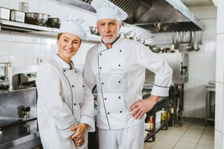 Photo for Female and male chefs in uniform looking at camera and smiling at restaurant kitchen - Royalty Free Image
