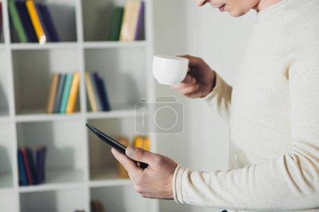 Photo pour Vue recadrée de l'homme cloutage avec ebook et tenant tasse de thé dans les mains - image libre de droit