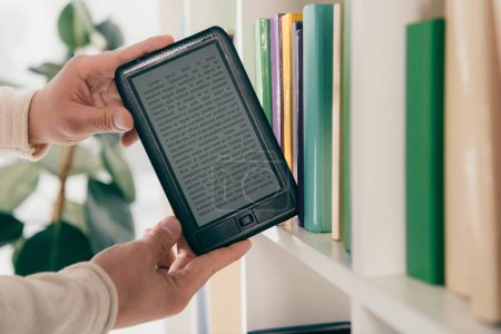Photo for Cropped view of man taking ebook from bookshelf - Royalty Free Image