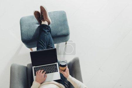 abgeschnittene Ansicht eines Mannes mit Pappbecher und Laptop mit leerem Bildschirm