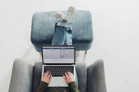 vue recadrée de la femme à l'aide d'un ordinateur portable avec facebook site à l'écran