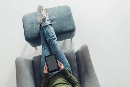 Photo pour Vue du dessus de la femme studing avec ebook et assis dans le fauteuil à la maison - image libre de droit